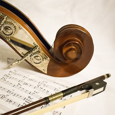 vrat violine sa vrhom gudala na stolu pored papira