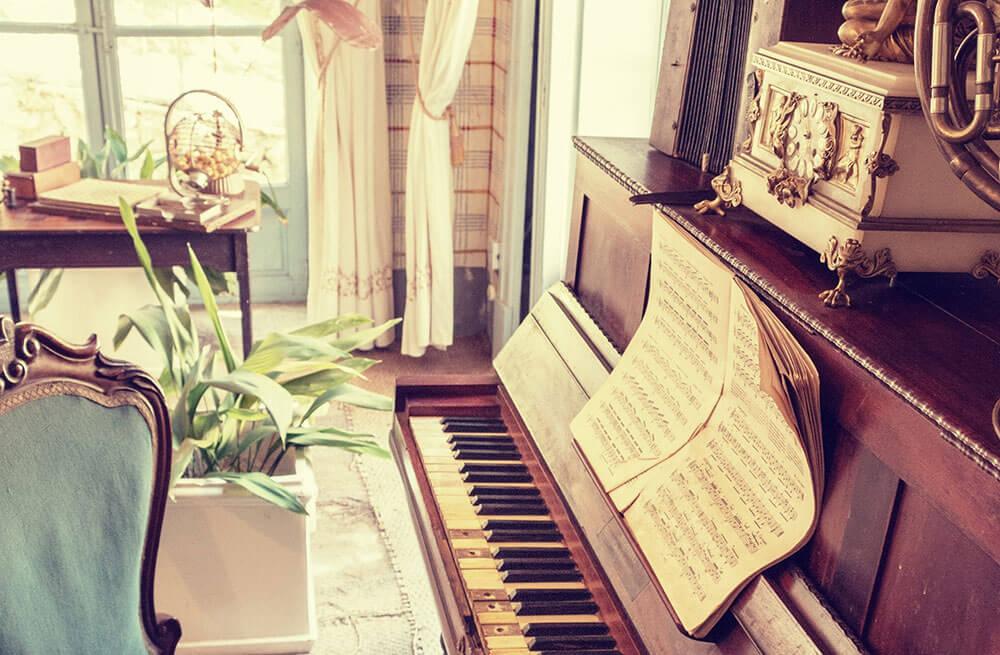 strai klavir pored prozora sa kiterom na klaviru